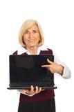 Femme aîné indiquant l'écran d'ordinateur portatif Images libres de droits