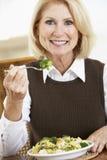 Femme aîné mangeant un repas sain images libres de droits