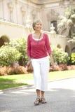 Femme aîné marchant par la rue de ville avec la carte photographie stock