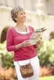 Femme aîné marchant par la rue de ville avec la carte photos stock