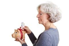 Femme aîné mettant l'argent dans porcin Photos stock