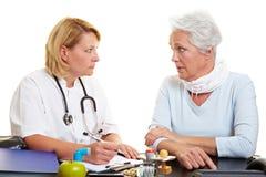 Femme aîné parlant au docteur Image libre de droits