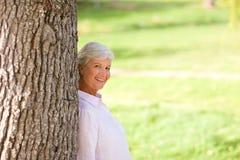 Femme aîné posant en stationnement Images stock