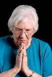 Femme aîné priant sur le noir Photos stock