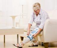 Femme aîné réglant le support de genou Photos libres de droits