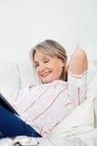 Femme aîné Relaxed avec le livre Image libre de droits