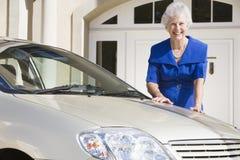 Femme aîné restant à côté du véhicule neuf Image stock