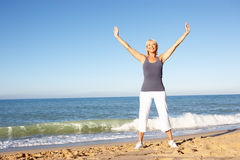 Femme aîné s'étirant sur la plage Image libre de droits