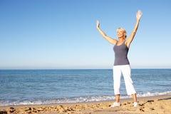 Femme aîné s'étirant sur la plage Photographie stock libre de droits