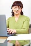 Femme aîné s'asseyant à la table avec l'ordinateur Image libre de droits