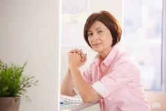 Femme aîné s'asseyant au bureau Image libre de droits