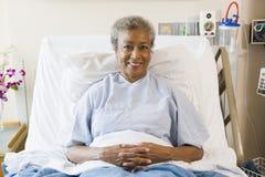 Femme aîné s'asseyant dans le bâti d'hôpital Photographie stock