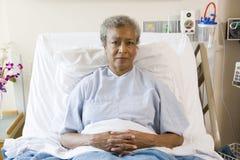 Femme aîné s'asseyant dans le bâti d'hôpital Photographie stock libre de droits