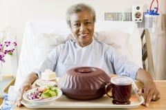 Femme aîné s'asseyant dans le bâti d'hôpital Image libre de droits