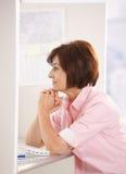 Femme aîné s'asseyant dans le bureau Images stock