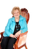 Femme aîné s'asseyant dans le fauteuil Photos libres de droits