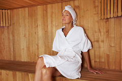 Femme aîné s'asseyant dans le sauna Image libre de droits