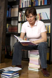 Femme aîné s'asseyant sur la pile de livre Photographie stock