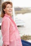 Femme aîné s'asseyant sur la plage Image stock