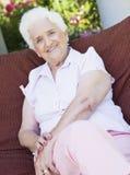 Femme aîné s'asseyant sur la présidence de jardin Photos libres de droits