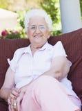 Femme aîné s'asseyant sur la présidence de jardin Photo stock
