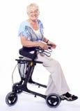 Femme aîné s'asseyant sur le marcheur Photographie stock