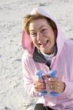 Femme aîné s'exerçant avec des poids de main sur la plage Photo stock
