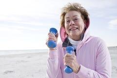 Femme aîné s'exerçant avec des poids de main sur la plage Photos libres de droits