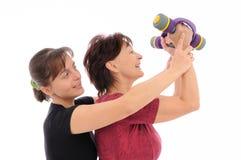 Femme aîné s'exerçant avec l'entraîneur Image libre de droits