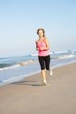 Femme aîné s'exerçant sur la plage Photographie stock