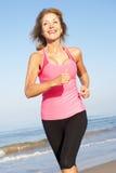 Femme aîné s'exerçant sur la plage Images stock