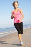 Femme aîné s'exerçant sur la plage Photos libres de droits