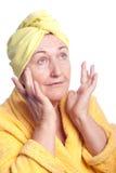 Femme aîné s'usant l'essuie-main jaune Image stock