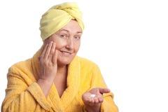 Femme aîné s'usant l'essuie-main jaune Photos stock