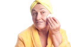 Femme aîné s'usant l'essuie-main jaune Photo libre de droits