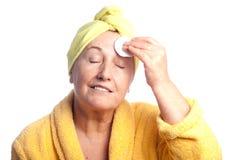 Femme aîné s'usant l'essuie-main jaune Image libre de droits