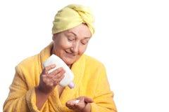 Femme aîné s'usant l'essuie-main jaune Photo stock