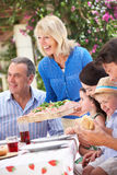 Femme aîné servant un repas de famille Photographie stock