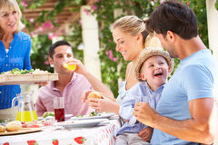 Femme aîné servant un repas de famille Images libres de droits