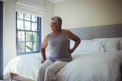 Femme aîné souffrant de la douleur dorsale à la maison Photos libres de droits