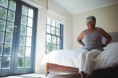 Femme aîné souffrant de la douleur dorsale à la maison Photo libre de droits