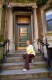 Femme aîné sur des opérations d'appartement de ville photo stock