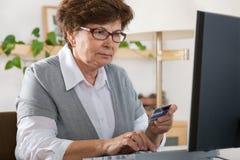 Femme aîné sur l'ordinateur Photos stock