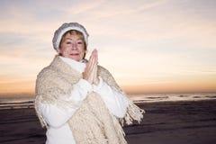 Femme aîné sur la plage dans le chapeau et le chandail de l'hiver Image libre de droits