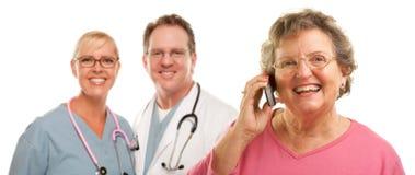 Femme aîné sur le téléphone portable et les médecins Behind Photo libre de droits
