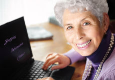 Femme aîné tapant sur l'ordinateur portatif Images stock