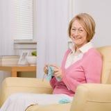 Femme aîné tricotant sur le sofa à la maison Photos stock