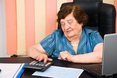 Femme aînée à l'aide de la calculatrice Photo stock