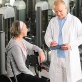 Femme aînée active d'aide de physiothérapeute à la gymnastique Photos stock