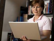 Femme aînée amicale restant avec l'ordinateur portatif Photos stock
